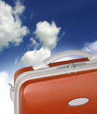 Orange suitcase in clouds. Red suitcase siting in the middle of a cloud in a surreal fashion with sky background Stock Photos