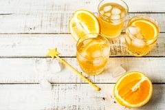 Orange summer drink with ice in glasses, bottle, fresh oranges on white background. Horizontal image stock images