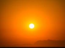 Orange summer sunset. Orange summer heat sunset with mountains silhouette Stock Image