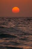Orange sun approaching horizon. Over sea royalty free stock image