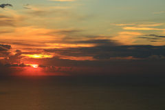 Orange sun hiding behind clouds Royalty Free Stock Images