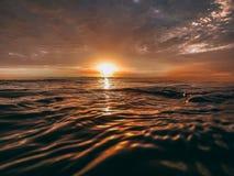 Orange sun over the ocean stock photos