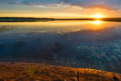 Orange sun and picturesque lake. On a calm summer morning Stock Photo