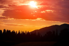 Orange Sun Setting Behind the Mountains Royalty Free Stock Photo