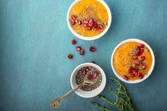 Orange sunda frukostsmoothies för Detox med säsongsbetonad mogen frukt, chiafrö, granatäpple på ett ljust kulört arkivfoton