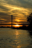 Orange sundown. The setting sun is [artially hidden by the highway bridge over the Waal river Stock Image