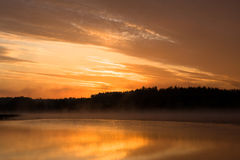 Orange sunrise. Above the river with golden clouds in the sky Royalty Free Stock Image