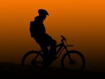 Orange sunrise. Mountain biker silhouette in orange sunrise royalty free stock photos