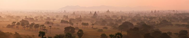 Orange mystical sunrise landscape view with silhouettes of old ancient temples and palm trees in dawn fog from balloon stock photos