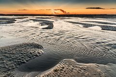 Sunrise on the sea at the Baie de Somme at low tide. Orange sunrise light on the mouth of the Somme River. The sky is reflected in the puddles of the low tide stock images
