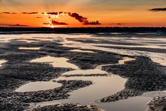 Sunrise on the sea at the Baie de Somme at low tide. Orange sunrise light on the mouth of the Somme River. The sky is reflected in the puddles of the low tide royalty free stock photography