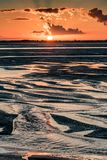 Sunrise on the sea at the Baie de Somme at low tide. Orange sunrise light on the mouth of the Somme River. The sky is reflected in the puddles of the low tide stock photo