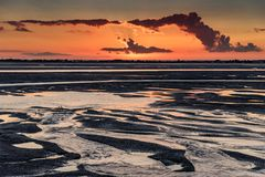 Sunrise on the sea at the Baie de Somme at low tide. Orange sunrise light on the mouth of the Somme River. The sky is reflected in the puddles of the low tide stock photography