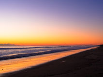 Orange sunrise on the long beach line Royalty Free Stock Photography