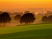 Orange sunrise over hilly farmland Royalty Free Stock Image