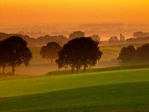 Orange sunrise over hilly farmland. Orange sunrise over misty and hilly farmland Royalty Free Stock Image