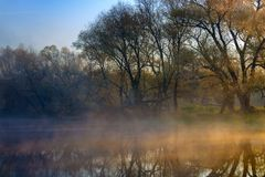 Orange sunrise over the river surface with fog in autumn morning. River landscape at sunrise Stock Photography