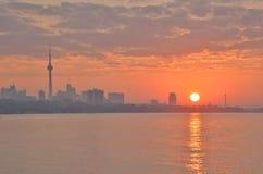 Orange sunrise reflected in Toronto bay with city skyline Stock Images