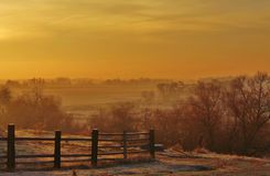 Orange sunrise. Rural sunrise with a fence in the foreground Stock Images