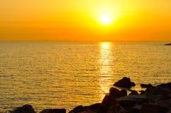 Orange sunrise in sea. Sunrise in sea with city on skyline Stock Photography