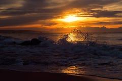 Orange sunrise with silhouette of splash. In Mui Ne, Vietnam Royalty Free Stock Image
