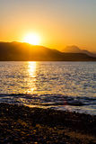 The orange sunrise under mountains and sea Royalty Free Stock Image