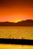 Orange Sunset. A man walking home from work on a sea wall with an orange sunset Royalty Free Stock Photography