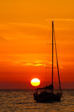 Orange sunset. Over water with the silhouette of a boats Stock Photos