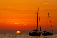Orange sunset. Over water with the silhouette of two boats Royalty Free Stock Photography
