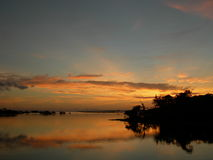 Orange sunset on the amazon river. Sun behind forest, symmetrical water and sky with scenic sunset on the amazon river stock photos