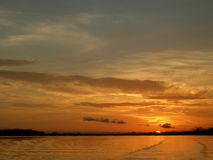 Orange sunset on the amazon river. Orange, symmetrical water and sky with scenic sunset on the amazon river royalty free stock photos