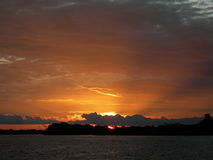 Orange sunset on the amazon river. Sun behind clouds, dark water and sky with scenic sunset on the amazon river stock photos
