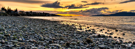 Panoramic Pebble Beach With Orange Sunset Royalty Free Stock Photos
