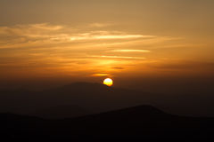 Orange sunset with clouds in mountains Royalty Free Stock Image