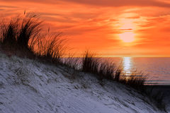 Orange sunset with dune and sea Stock Photo