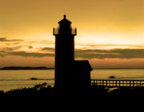 Orange sunset lighthouse. Lighthouse back lit by an orange sunset with two boats zooming by in the background Royalty Free Stock Photo