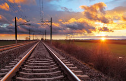 Orange sunset in low clouds over railroad.  Royalty Free Stock Image
