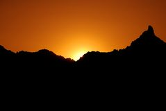 Orange Sunset with Mountains. A stunning orange sun setting behind the silhouette of a craggy mountain in the Arizona desert-this shot is available in horizontal stock photos