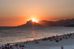 Orange sunset by the ocean in Piratininga, Niteri, with sun dipping behing the Gavea Stone in Rio de Janeiro. A beach full of peop. Le can be seen in the royalty free stock images