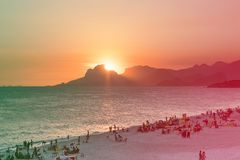 Orange sunset by the ocean in Piratininga, Niteri, with sun dipping behing the Gavea Stone in Rio de Janeiro. A beach full of peop. Le can be seen in the royalty free stock image