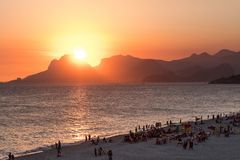 Orange sunset by the ocean in Piratininga, Niteroi, with sun dipping behing the Gavea Stone in Rio de Janeiro. A beach full of peo. Orange sunset by the ocean in stock photos