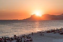 Orange sunset by the ocean in Piratininga, Niteroi, with sun dipping behing the Gavea Stone in Rio de Janeiro. A beach full of peo. Orange sunset by the ocean in stock photo