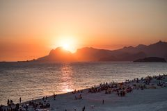Orange sunset by the ocean in Piratininga, Niteroi, with sun dipping behing the Gavea Stone in Rio de Janeiro. A beach full of peo. Orange sunset by the ocean in royalty free stock photography