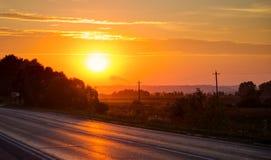 Orange sunset over asphalt road Royalty Free Stock Image
