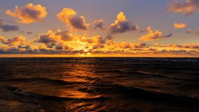 Orange sunset over Baltic sea shoreline with clouds and reflection in waves, selective focus.  stock photos