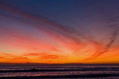Orange sunset over beach. Scenic view of orange sunset and cloudscape over Newport beach and ocean, California, U.S.A royalty free stock photo