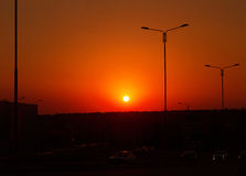 Orange sunset over the city. Urban sunset. On the horizon of the forest. Cars driving on the road Stock Photography