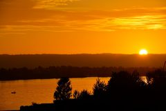 ORANGE SUNSET OVER THE COLUMBIA RIVER. Sun setting over a fishing boat on the Oregon and Washington border Royalty Free Stock Photo
