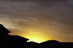 Orange sunset over houses. Bright orange western sunset over houses Royalty Free Stock Image