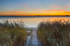 Orange Sunset over Jetty on the shore of a Lake Royalty Free Stock Image